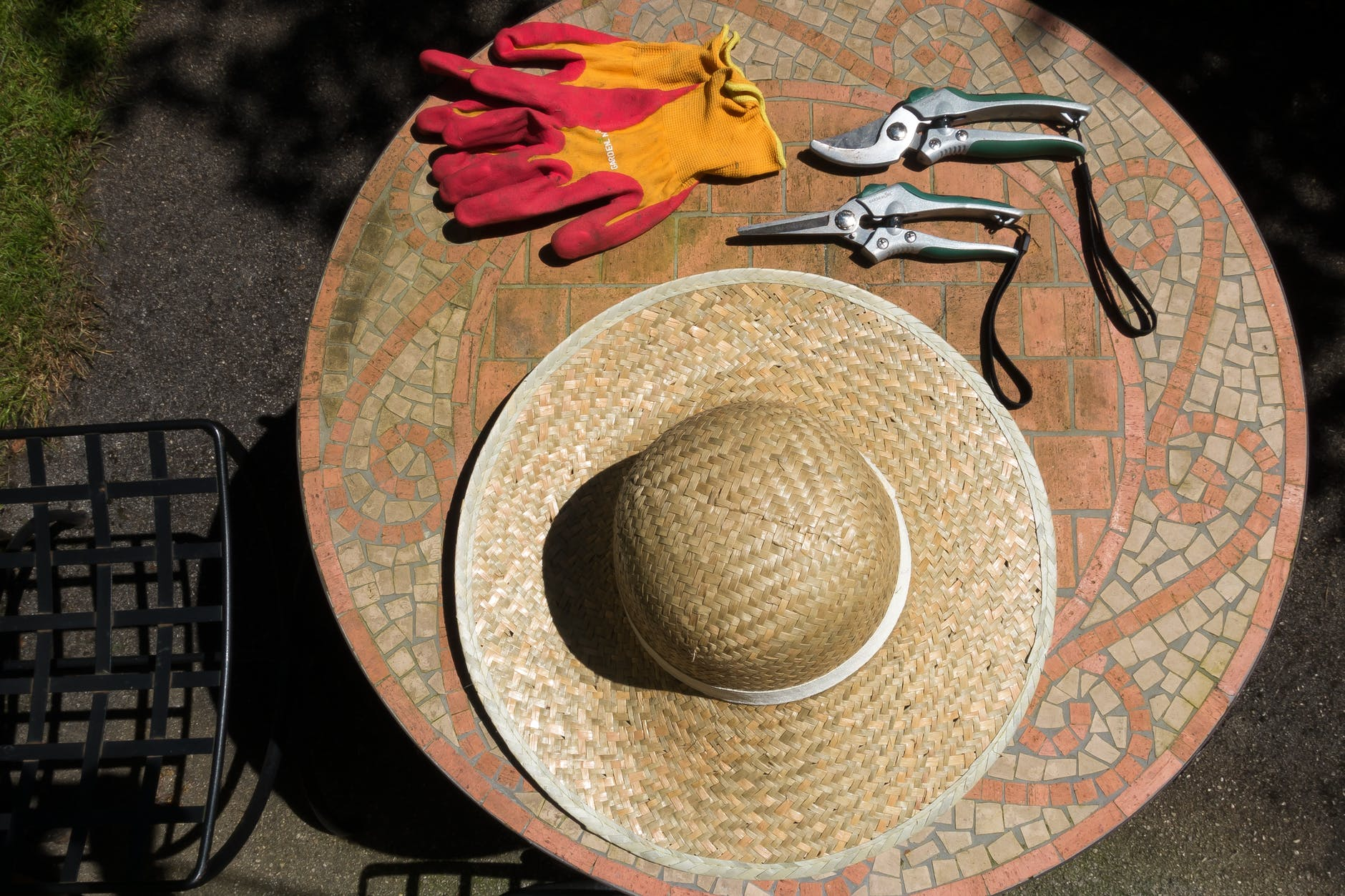 Outdoor table with wide brimmed hat, garden gloves and hand held pruners
